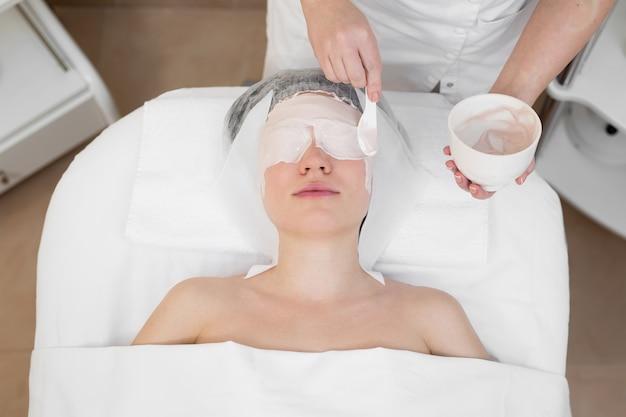 Maschera peeling viso, trattamento di bellezza termale, cura della pelle. donna che ottiene cura del viso dall'estetista al salone della stazione termale. la donna fa una maschera di alginato.
