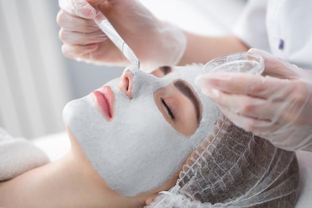 Maschera peeling viso, trattamenti di bellezza spa, cura della pelle. donna che ottiene cura del viso dall'estetista al salone della stazione termale