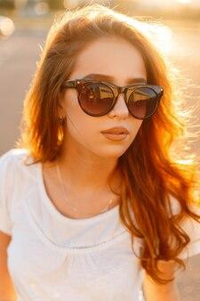 Ritratto del fronte di una donna rossa bella carina giovane hipster in occhiali da sole alla moda in una maglietta bianca alla moda in un parco di divertimenti