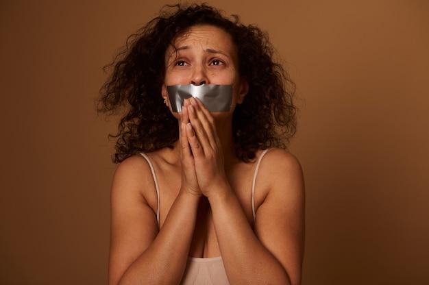Il ritratto del volto di una donna ispanica di razza mista disperata spaventata con la bocca sigillata cerca con una richiesta di aiuto. concetto sociale della giornata internazionale per l'eliminazione della violenza contro le donne