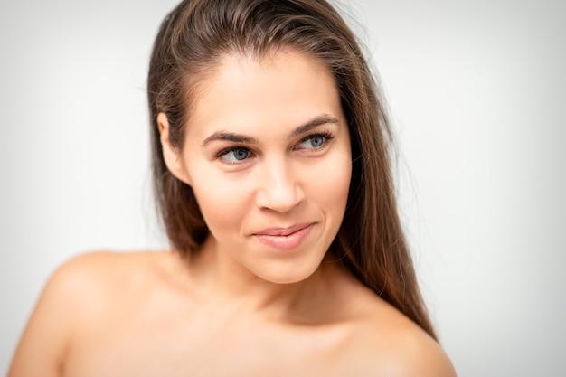 Ritratto del fronte di giovane donna caucasica con spalle nude e trucco naturale su priorità bassa bianca