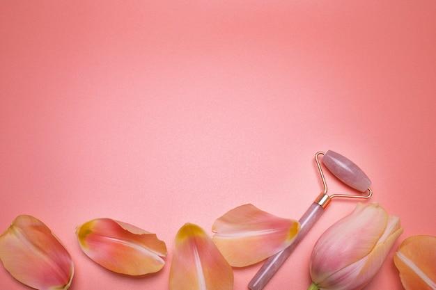 Rullo facciale e petali sullo sfondo rosa con spazio libero per il testo strumento per il massaggio facciale