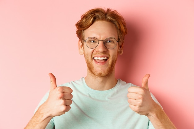 Volto di cliente maschio soddisfatto che mostra pollice in su in segno di approvazione, sorridente felice, indossando occhiali e t-shirt, sfondo rosa.