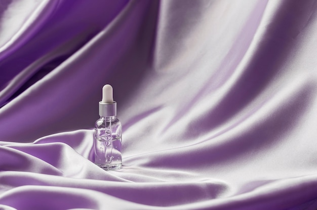Siero per il viso su sfondo di tessuto piegato seta lilla. prodotto di bellezza cosmetico di lusso.