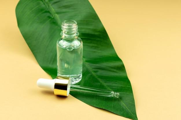 Siero viso in flacone di vetro trasparente su foglia verde e fondo beige. trattamento per la pelle con oli, vitamine e collagene. confezione senza marchio di prodotti cosmetici di bellezza.
