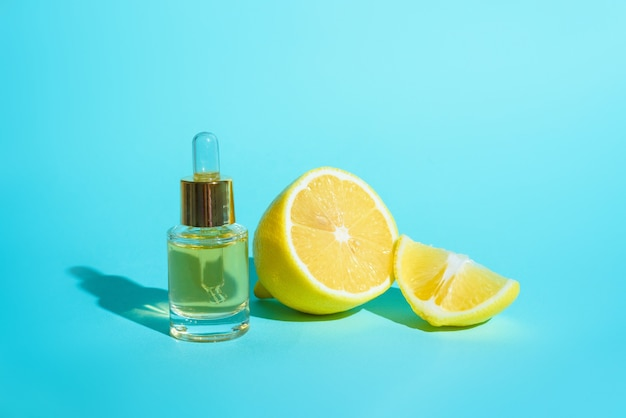 Siero per il viso con agrumi, limone e vitamina c in una bottiglia di vetro con una pipetta su sfondo blu, il concetto di cura della pelle di auto-cura a casa.