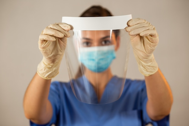Visiera in mani con guanti di gomma davanti a una testa sfocata dell'infermiera