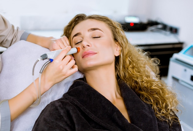 Cura della pelle del viso. primo piano della donna riccia abbastanza bionda che ottiene trattamento di peeling idro microdermoabrasione facciale alla clinica della stazione termale di cosmetologia. aspirapolvere hydra.