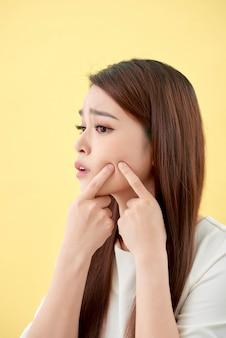 Problema della pelle del viso - giovane donna infelice tocca la sua pelle isolata, concetto per la cura della pelle, asiatica