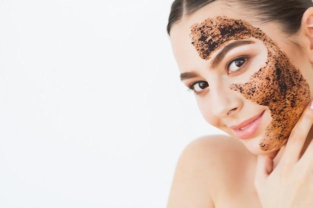 Cura della pelle del viso. giovane ragazza affascinante fa una maschera nera al carbone sul viso.
