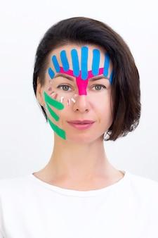 Nastratura del viso, primo piano del viso di una ragazza con nastro cosmetologico antirughe. nastratura estetica del viso. metodo lifting antietà non invasivo per la riduzione delle rughe. foto verticale