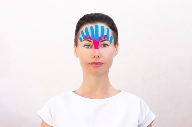 Nastratura del viso, primo piano del viso di una ragazza con nastro cosmetologico antirughe. nastratura estetica del viso. metodo lifting antietà non invasivo per la riduzione delle rughe