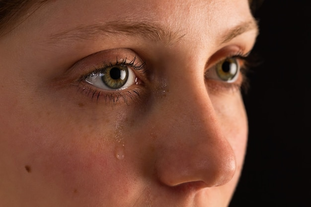 Volto di donna infelice in lacrime da vicino nell'oscurità.