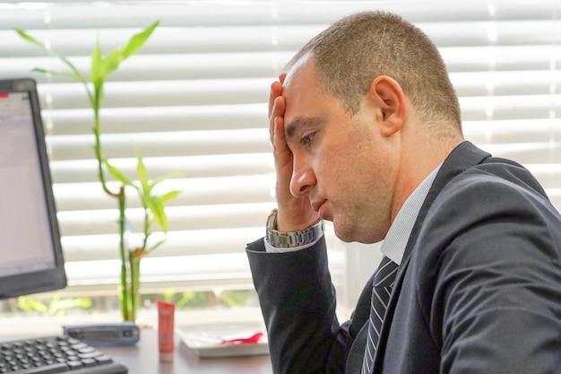 Volto di impiegato sconvolto, uomo manager in stress davanti al monitor del computer