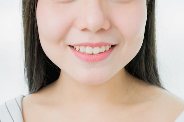Il viso di una donna con una buona salute della pelle sorride e le labbra rosa.