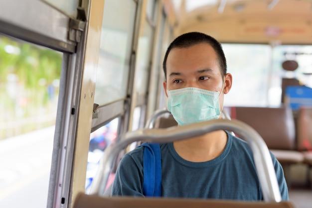 Volto di giovane uomo asiatico con maschera in sella al bus con la distanza
