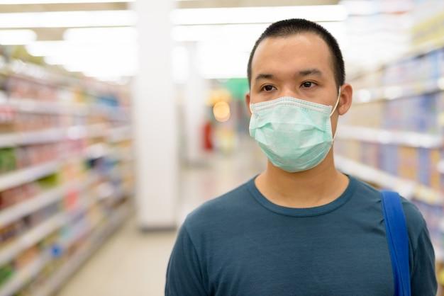 Volto di giovane uomo asiatico con maschera shopping con distanza al supermercato