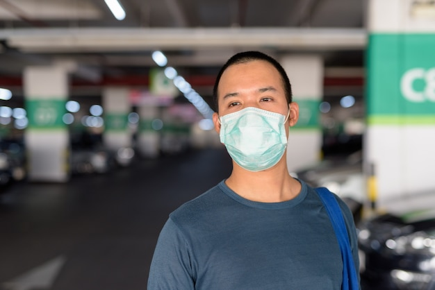 Volto di giovane uomo asiatico con maschera pensando al parcheggio