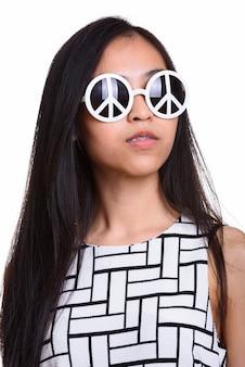 Volto di giovane ragazza adolescente asiatica che indossa occhiali da sole con occhiali da sole di pace