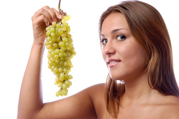 Il volto di un primo piano di una giovane ragazza, un grappolo di uva verde matura