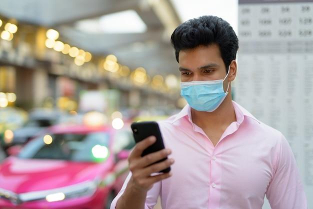 Volto di giovane uomo d'affari indiano con maschera utilizzando il telefono alla fermata dell'autobus