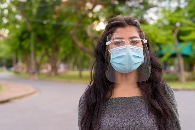 Volto di giovane donna indiana che indossa maschera e visiera al parco all'aperto