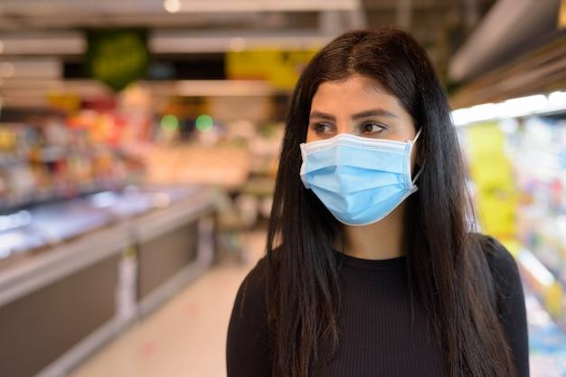 Volto di giovane donna indiana con maschera pensando e facendo acquisti con la distanza al supermercato