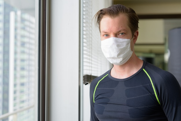 Volto di giovane uomo con maschera per protezione dall'epidemia di coronavirus pronto per l'esercizio durante il covid-19