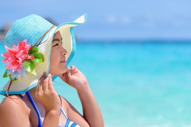 Faccia giovane donna che indossa il cappello di protezione solare è felice di vedere la bellissima natura del mare e della spiaggia sotto il cielo estivo a koh miang island nel parco nazionale mu ko similan, phang nga, thailandia