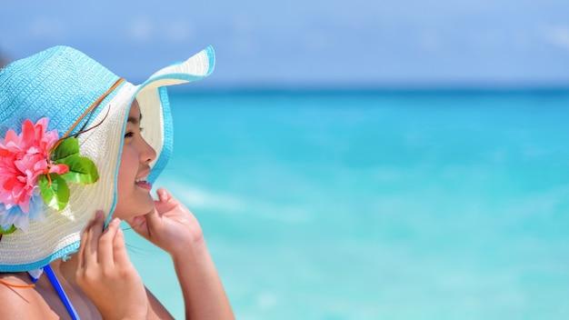 Faccia giovane donna che indossa il cappello di protezione solare è felice di vedere la splendida natura del mare sotto il cielo estivo a koh miang island nel parco nazionale mu ko similan, phang nga, thailandia, wide screen 16:9