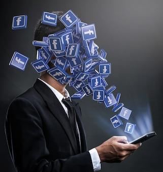 Icone di facebook che spuntano in faccia a un uomo