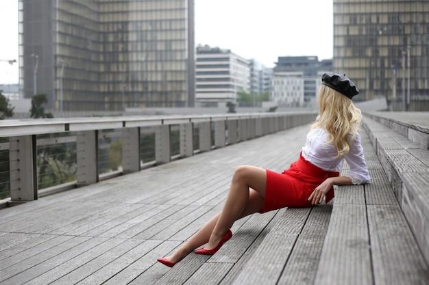 Bionda senza volto in camicetta bianca, gonna corta rossa e berretto in pelle nera si siede sui gradini grigi di parigi. moda di strada