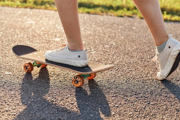 Skateboard femminile senza volto all'aperto su strada asfaltata in estate, trascorrendo il tempo in modo attivo, pattinatore sconosciuto si muove su uno skateboard lungo la strada.