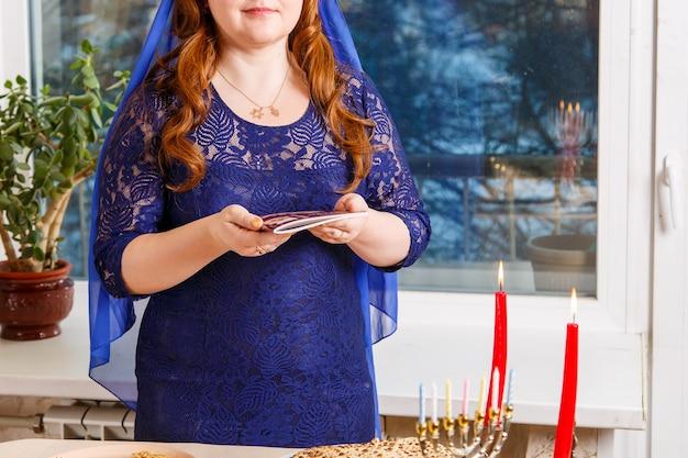 Una donna ebrea senza volto al tavolo del seder pasquale legge la haggadah pasquale