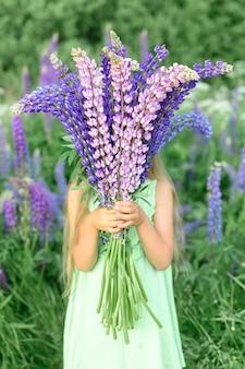Bambina senza volto con bouquet di lupini fioriti