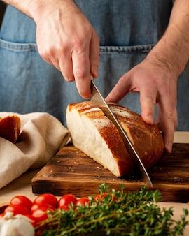 Uomo senza volto che taglia il pane croccante cotto domestico fresco con il grande coltello