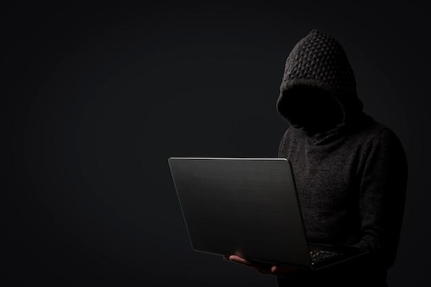 L'uomo senza volto in una felpa con cappuccio con cappuccio tiene un computer portatile in mano su sfondo scuro. il concetto di hacking e furto di dati utente