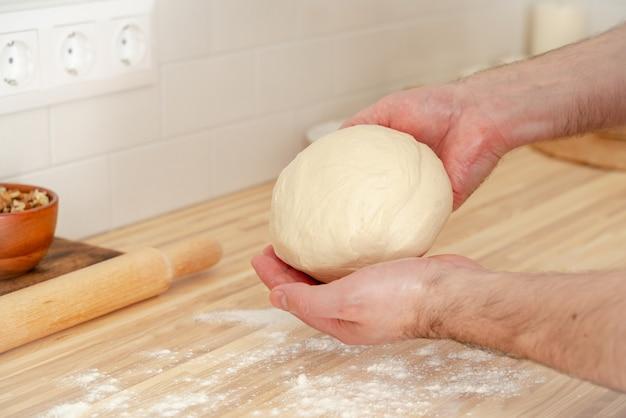 Uomo senza volto che impasta la pasta sul tavolo della cucina a casa,