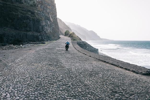 Persona senza volto in sella a una moto su una strada deserta