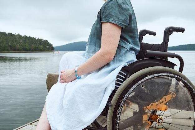 Ritratto senza volto di una donna su una sedia a rotelle sullo sfondo della natura.
