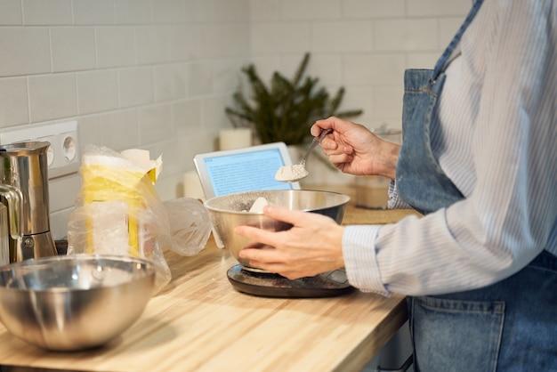 Donna senza volto cucinare e cuocere la pasta sul tavolo della cucina a casa