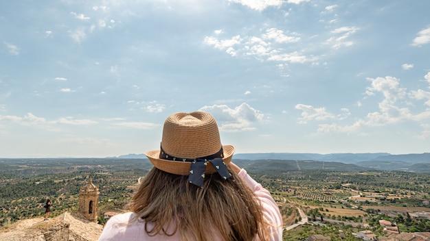 Donna senza volto in un paesaggio di campagna con ulivi da una torre