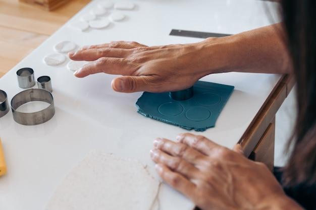 Donna senza volto che crea gioielli fatti a mano usando l'argilla e lavorando da casa.