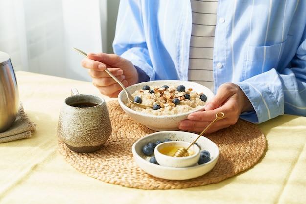 La donna senza volto mangia la colazione, porridge di farina d'avena con frutti di bosco e noci, cibo sano