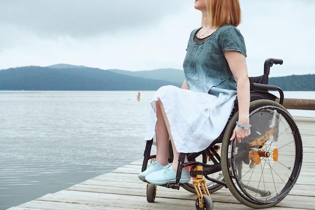 Donna senza volto in sedia a rotelle che gode di una splendida vista sul mare o sul lago.