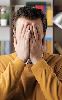 Palma facciale. l'uomo barbuto stupito con gli occhiali in ufficio o nella stanza dell'appartamento guarda la telecamera e si copre il viso con le mani esprimendo il suo sconcerto. vista ravvicinata
