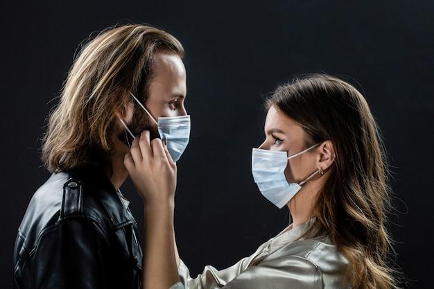 Volti di persone con maschere protettive dal coronavirus. bella coppia in quarantena. coppia che indossa una maschera protettiva, pandemia e concetto di sentimenti. stile di vita covid-19.
