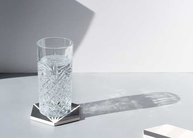 Bicchiere sfaccettato di acqua pulita fresca con ombra sul tavolo grigio, spazio copia, luce dura. bevanda minerale estiva rinfrescante, bevanda fredda salutare per l'idratazione. acqua cristallina