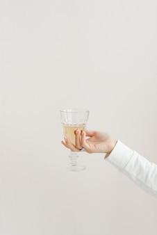Bicchiere di vetro sfaccettato nelle mani di una ragazza in un bicchiere di vestiti bianchi