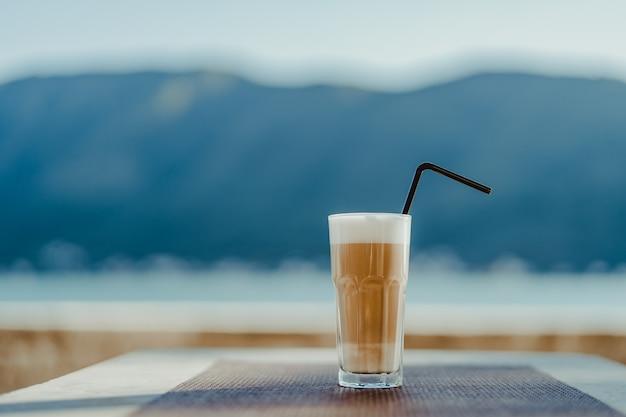 Vetro sfaccettato con caffè latte e una cannuccia. spazio vuoto per il testo.
